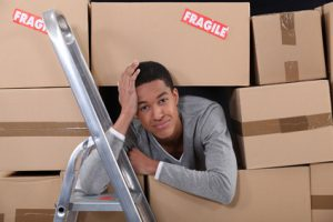 young man surrounded by boxes apartment